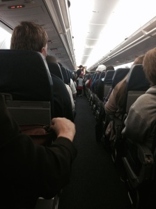 A bit far away, but the flight attendant is leading Paige to the front of the plane, where she got to meet the pilots and see the cockpit.